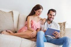 Hipsterpar genom att använda minnestavlan på soffan Royaltyfri Fotografi
