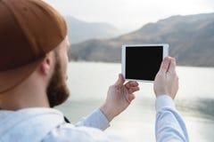 Hipsterpersoninnehav i digital minnestavla för händer med den tomma tomma skärmen, manfotografi på datoren på bakgrundsnaturen Royaltyfria Foton