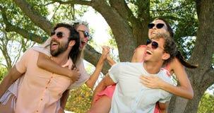 Hipsterpojkar som bär flickor på deras skuldra lager videofilmer