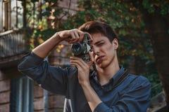 Hipsterpojkefotograf med den retro kameran fotografering för bildbyråer