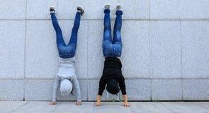 Hipsters die handstand doen tegen muur in stad Royalty-vrije Stock Fotografie