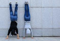 Hipsters die handstand doen tegen muur in stad Stock Afbeeldingen