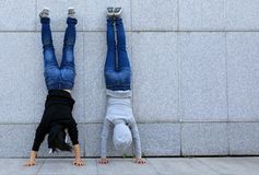 Hipsters doing handstand against wall in city Stock Images
