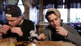 Hipsters eating delicious roasted chicken wings stock footage