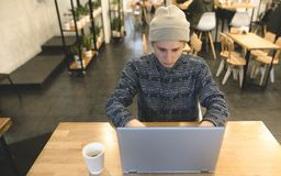 Hipsters freelance works in a cozy cafe for a laptop. A student uses a laptop in a cafe for a cup of coffee. Hipsters freelance works in a cozy cafe for a Royalty Free Stock Photography