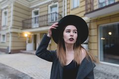 A hipsters girl poses a camera around the beautiful old architecture. Evening portrait of a stylish woman against the backdrop of a yellow house Stock Photos