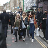 Hipsters girls dressed in cool Londoner style walking in Brick lane, a street popular among young trendy people Stock Photo
