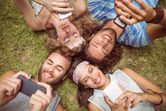 Hipsters lying on grass using smartphones Stock Image