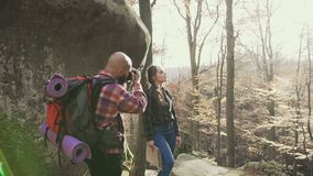 Hipsters in the mountains. A young man photographer photographing a beautiful girl with long hair braided in a braid stock video