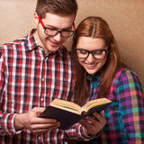 Hipsters reading a book. Stock Photos