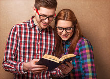 Hipsters reading a book. Royalty Free Stock Image