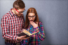 Hipsters reading a book. Stock Images