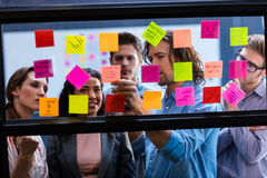 Hipsters reading a post it on a window. In the office Royalty Free Stock Image