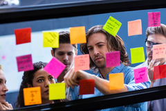 Hipsters reading a post it on a window. In the office Royalty Free Stock Photography