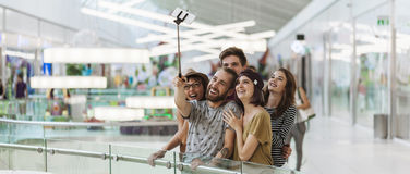 Hipsters In Shopping Mall Taking Selfie. Group Of Hipsters In Shopping Mall Taking Selfie Using Smart Phone And Monopod royalty free stock photography