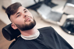 Hipsters sitting on a chair in the barbershop. Looking to the top Stock Image