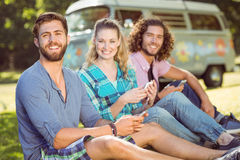 Hipsters sitting on the grass texting Royalty Free Stock Photography