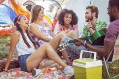 Hipsters som har gyckel i deras campingplats arkivbild