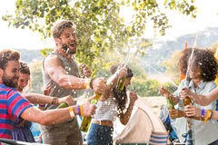 Hipsters spraying beer over each other Royalty Free Stock Photography