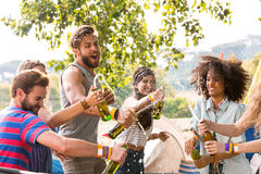 Hipsters spraying beer over each other Royalty Free Stock Photos