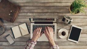 Hipsterskrivbord med manliga händer Fotografering för Bildbyråer