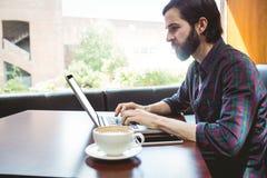 Hipsterstudent som använder bärbara datorn i kantin fotografering för bildbyråer