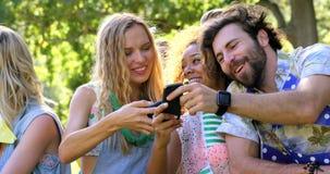 Hipstervänner som ser deras mobiltelefon- och minnestavladator lager videofilmer