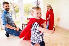 Hipstervader met zijn prinsesdochters die rode kaap dragen Stock Afbeeldingen