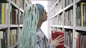 Hipstervrouw die een boek in bibliotheek lezen stock footage