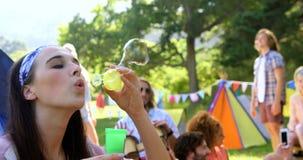 Hipstervrouw die zeepbel met een stuk speelgoed doen stock footage