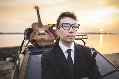 Hipter in glasses and his guitar on car rack Stock Images