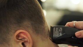 Hirdresser que faz o corte de cabelo com lâmina elétrica Feche acima do cabelo do corte do barbeiro com a máquina profissional do vídeos de arquivo
