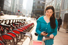 Hire bike. Young woman with a hire bike checking her phone Stock Photography