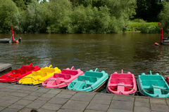 Hire boats. A row of multicoloured boats lined up next to a river bank pavement with trees on the far shore Stock Photos