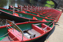 Hire boats on river Nidd, Knaresborough, UK. Riverside view of rowing hire boats in Knaresborough, taken from the bank of river Nidd in bright summer sunlight in Royalty Free Stock Photo