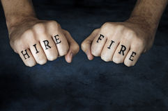 Hire or Fire?. Conceptual image of a man with HIRE and FIRE fake tattoos royalty free stock images