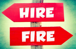 Hire or fire. Hire and fire concept on the red signs with landscape in background Royalty Free Stock Images