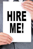 Hire me. A man wearing a suit holding a signboard with the text hire me written on it stock photography