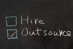 Hire or outsource. Choosing from hire and outsource concept words on blackboard stock image