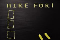 Hire For! written with color chalk. Supported by an additional services. Blackboard concept stock photos