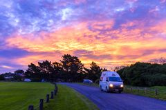 Hired camper driving into a campsite. One of thousands rental campers driving into a free campsite near Brighton, New Zealand stock image