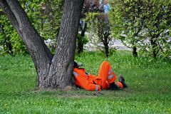 Tired worker resting on the grass. Tired road worker resting on the grass Stock Photo