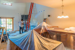 Hired painter painting a home. With all furniture covered Royalty Free Stock Photography