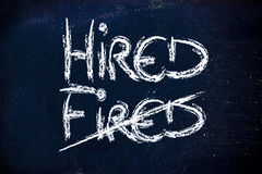 Hired vs. fired message on chalkboard. Chalk writings on blackboard, finding a job again Stock Photo