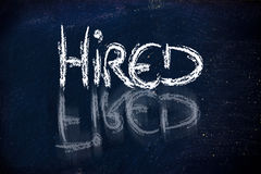 Hired vs. fired message on chalkboard. Chalk writings on blackboard, finding a job again Royalty Free Stock Photography