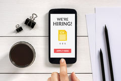 We are hiring apply now concept on smartphone screen with office Royalty Free Stock Photos