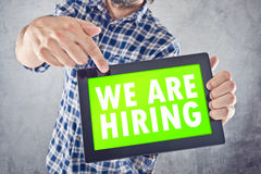 We Are Hiring. Casual businessman pointing to digital tablet device with We Are Hiring title displayed on Touchscreen Royalty Free Stock Photography