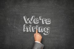 We are hiring concept. On black blackboard with businessman hand stock image