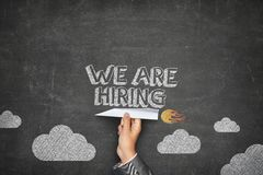 We are hiring concept. On black blackboard with businessman hand holding paper plane stock photography