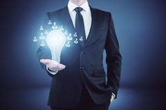 Hiring concept. Businessman holding glowing lamp with hr icons in abstract gradient interior. Hiring concept Stock Photo
